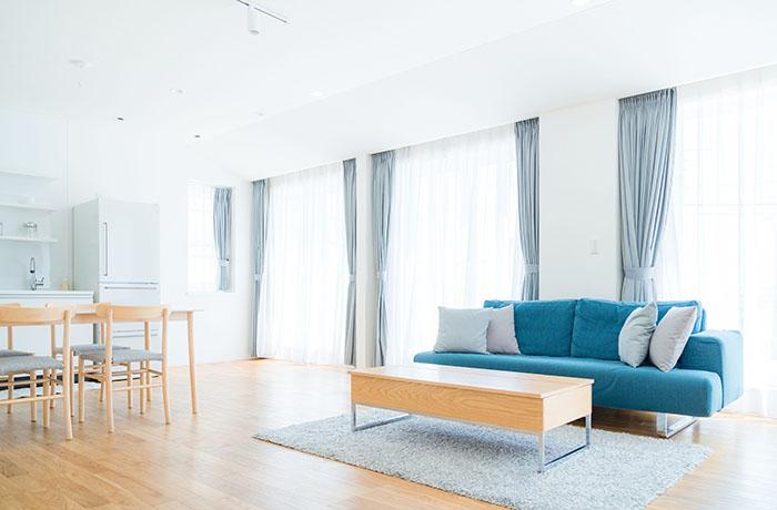 青いソファの置かれた広々としたリビング