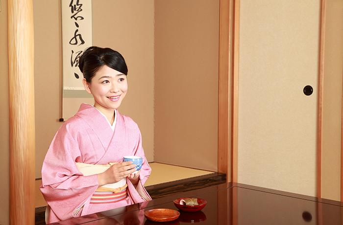 和室でお茶を飲む着物の女性