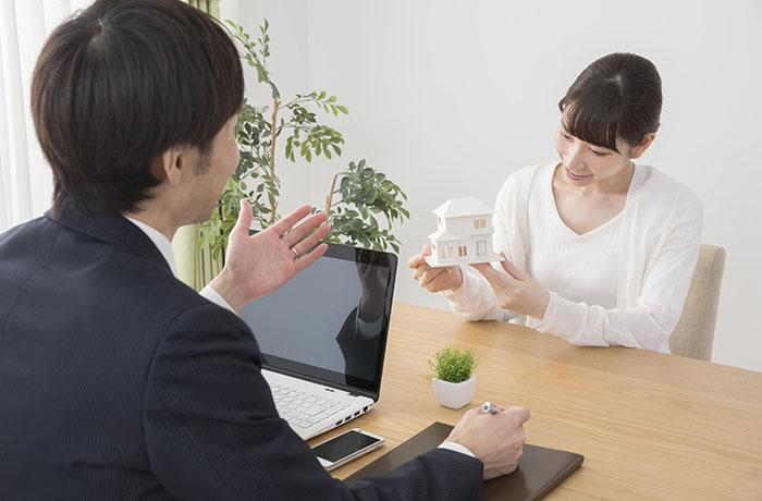 家の模型を眺める女性と説明中の男性
