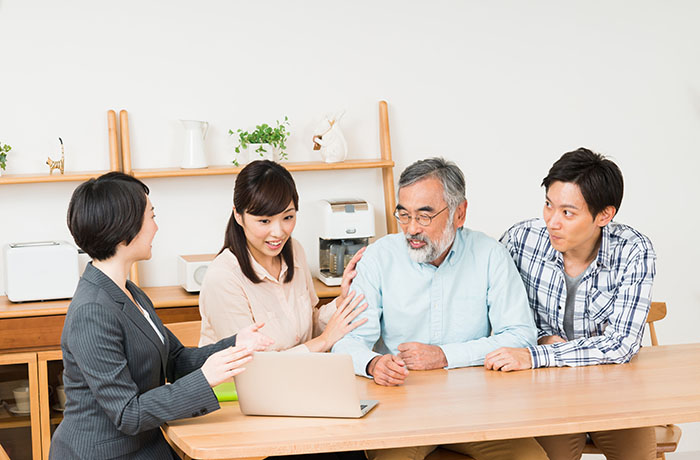 ノートパソコンを見ながら話し合うスタッフと家族